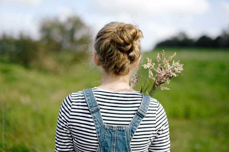 Back view of girl holding long flowering grass over her shoulder by Jacqui Miller for Stocksy United