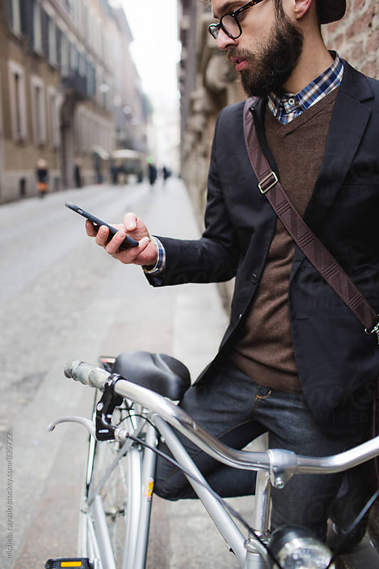Young man with a beard using his cell phone outdoors by michela ravasio for Stocksy United