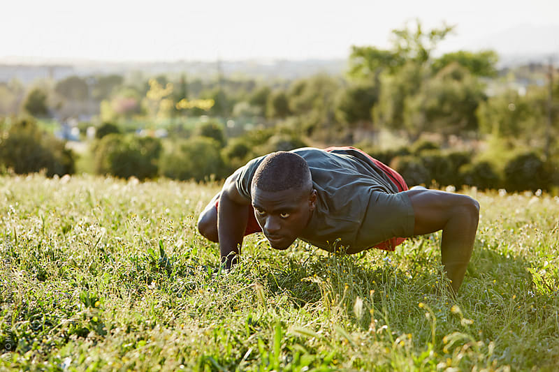 Determined Male Athlete Doing Push-Ups On Grass by ALTO IMAGES for Stocksy United