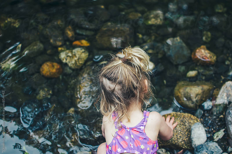 Little girl playing in river by Dominique Chapman for Stocksy United