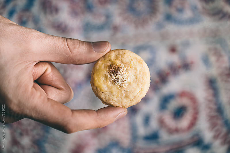 Fingers holding a cookie over table cloth by Lior + Lone for Stocksy United