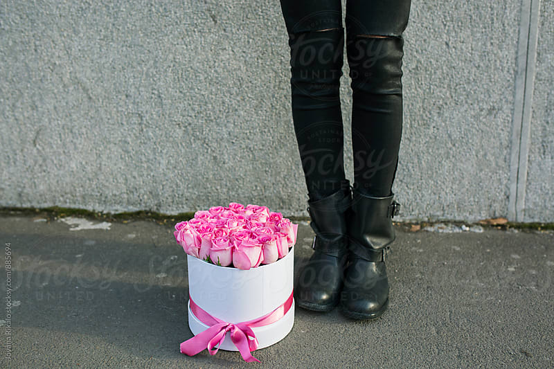 Girl's legs and box full of pink roses  by Jovana Rikalo for Stocksy United