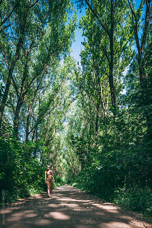 Young woman in summer dress walking at camera on park alley by Ilya for Stocksy United