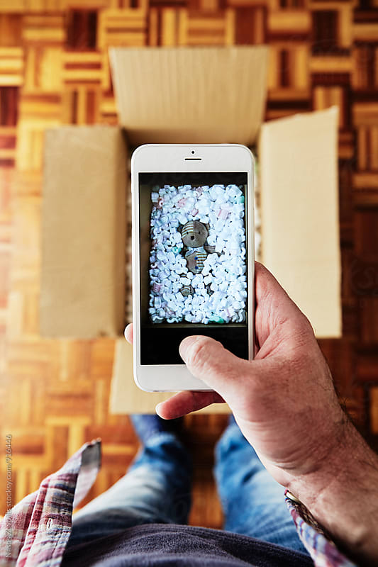 Man taking picture of a teddy bear in a box by Nasos Zovoilis for Stocksy United