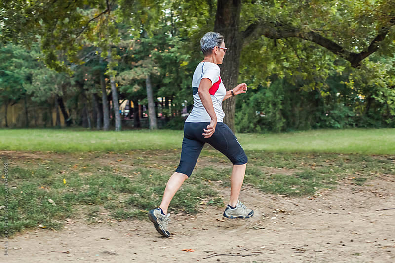 Senior woman runs at the park by Jelena Jojic Tomic for Stocksy United