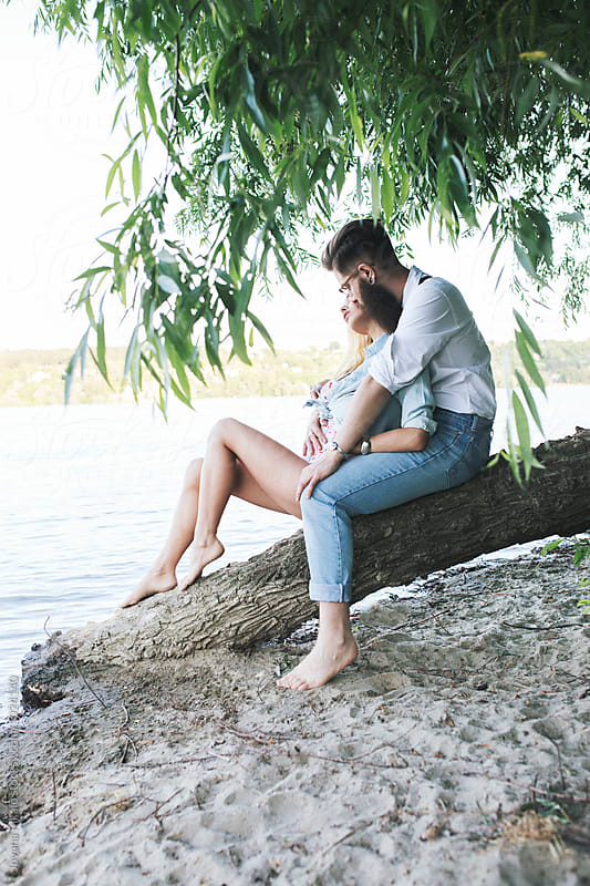 Happy young couple on the beach by Jovana Rikalo for Stocksy United
