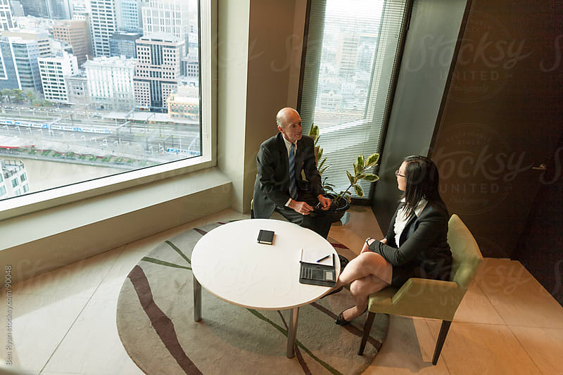 Senior male and female executives chatting with city views in ba by Ben Ryan for Stocksy United