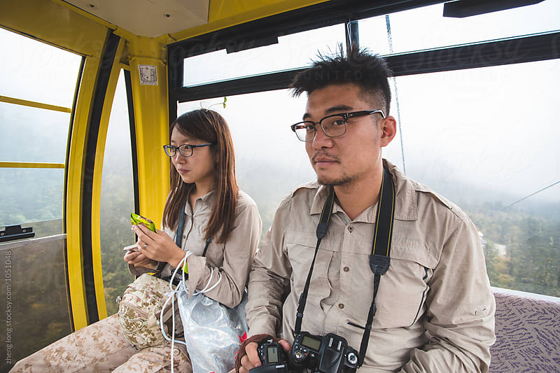 young couple in the funicular by zheng long for Stocksy United