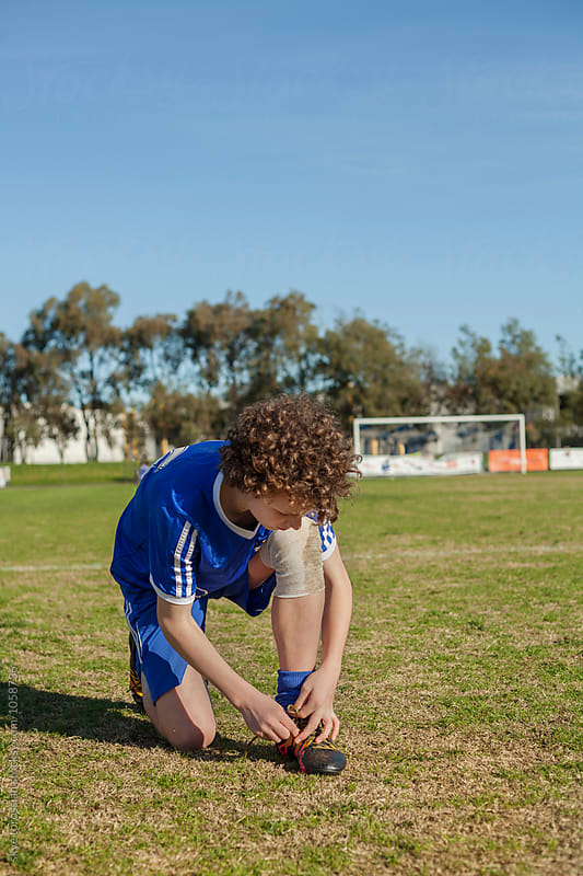 Teen boy preparing for football game by skye torossian for Stocksy United