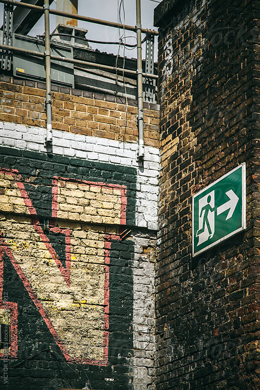 Brick Wall Background with an Exit Green Sign by Victor Torres for Stocksy United