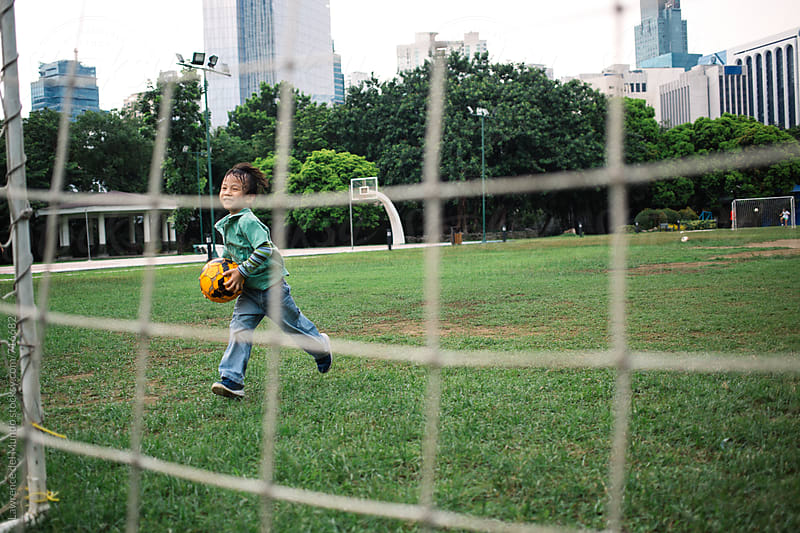 A young kid running and happily carrying a football in his hands in the park. by Lawrence del Mundo for Stocksy United
