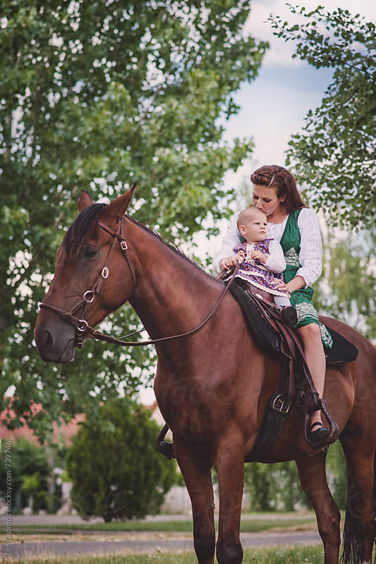 Baby girl riding a horse with her mother by Lea Csontos for Stocksy United