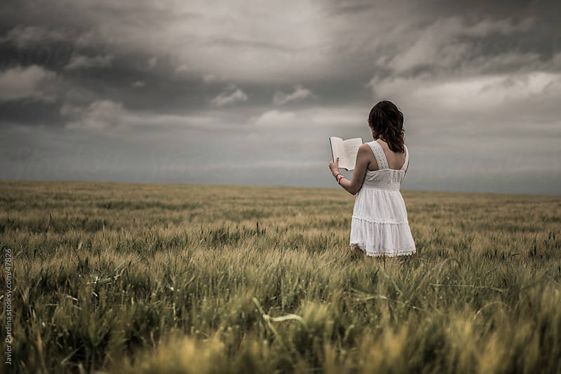 woman in white dress in the middle of the field reading for the storm by Javier Pardina for Stocksy United