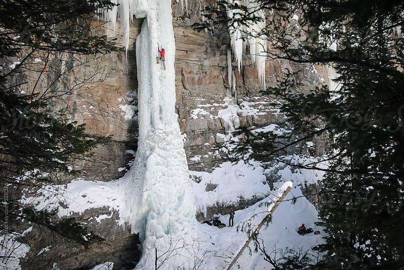 Ice climber on tall steep pillar of ice  by Mick Follari for Stocksy United
