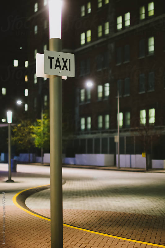 Taxi sign in the city by Lauren Naefe for Stocksy United