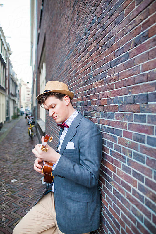 Young man in a classic suit playing a ukelele by Ivo de Bruijn for Stocksy United