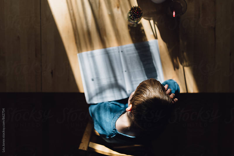 boy with head on his hand, trying to do schoolwork by Léa Jones for Stocksy United