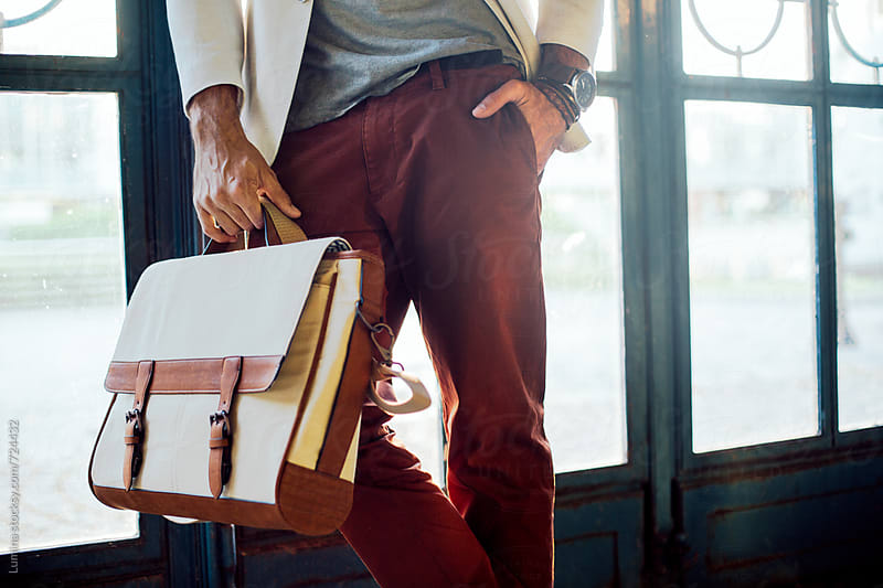 Stylish Man Holding a Handbag by Lumina for Stocksy United