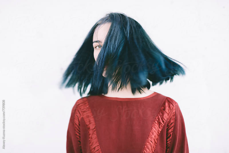 young woman flicking her blue hair by Alexey Kuzma for Stocksy United