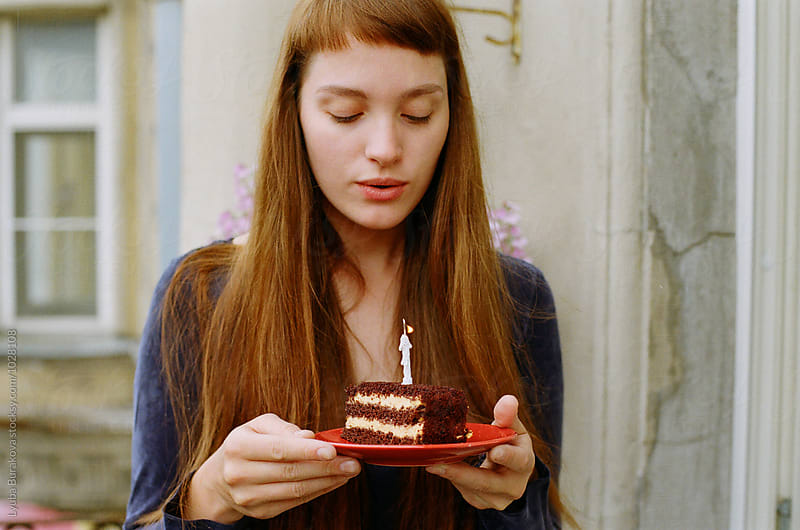 Woman blowing out Birthday candle by Liubov Burakova for Stocksy United