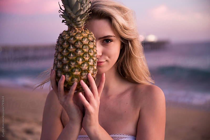 Beautiful blonde girl holding a pineapple  by Curtis Kim for Stocksy United