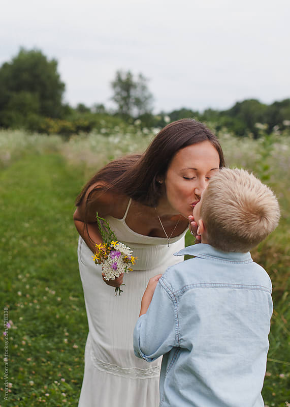 Mother kisses son after he gives her a bouquet of wildflowers by Amanda Worrall for Stocksy United