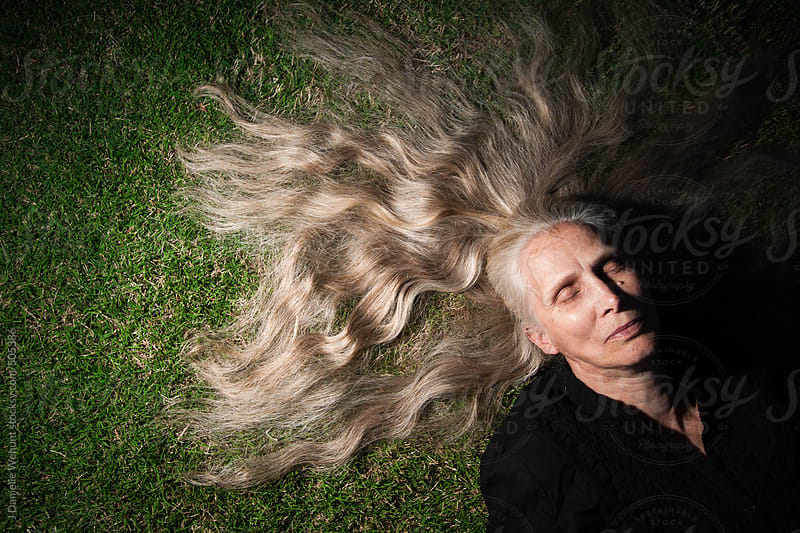 elderly woman laying on ground with long blonde hair fanned out over grass by J Danielle Wehunt for Stocksy United