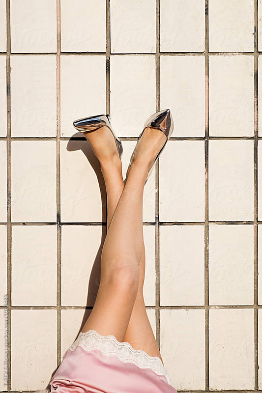 Close-up of girl's legs in silver heels against of stone wall by T-REX & Flower for Stocksy United