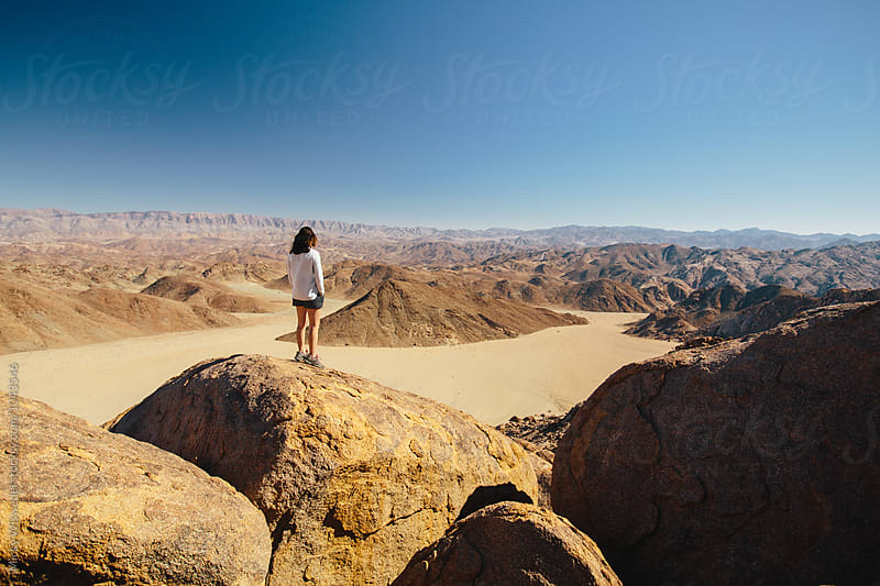 Hiker on a mountain summit overlooking an expansive desert view by Micky Wiswedel for Stocksy United