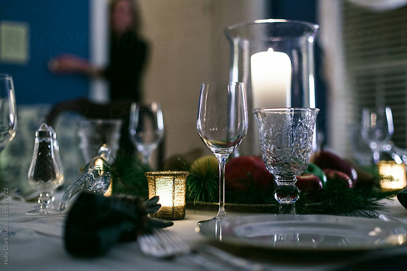 A woman turns the lights down on a formal table set for Thanksgi by Holly Clark for Stocksy United