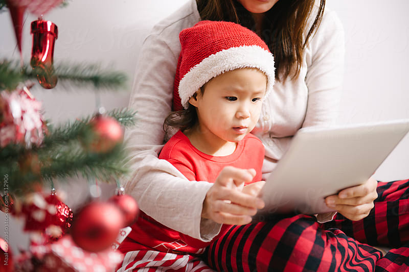 Toddler girl and her mother using digital PC by christmas tree by MaaHoo Studio for Stocksy United