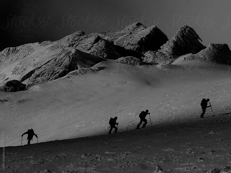 Four alpinists with backpacks climbing up the mountain by rolfo for Stocksy United