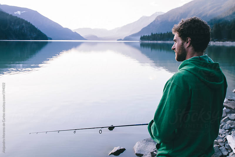 Young man fishing on a lake by Alejandro Moreno de Carlos for Stocksy United