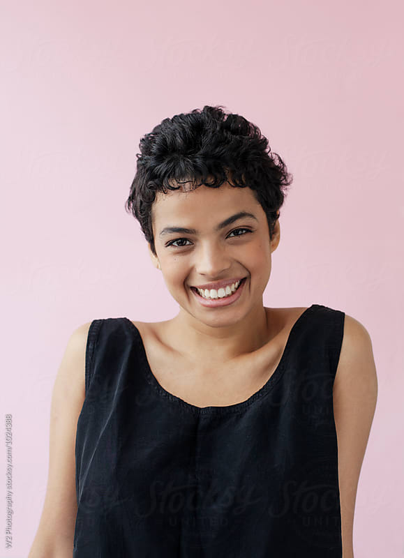 Portrait of smiling young woman with pink background.