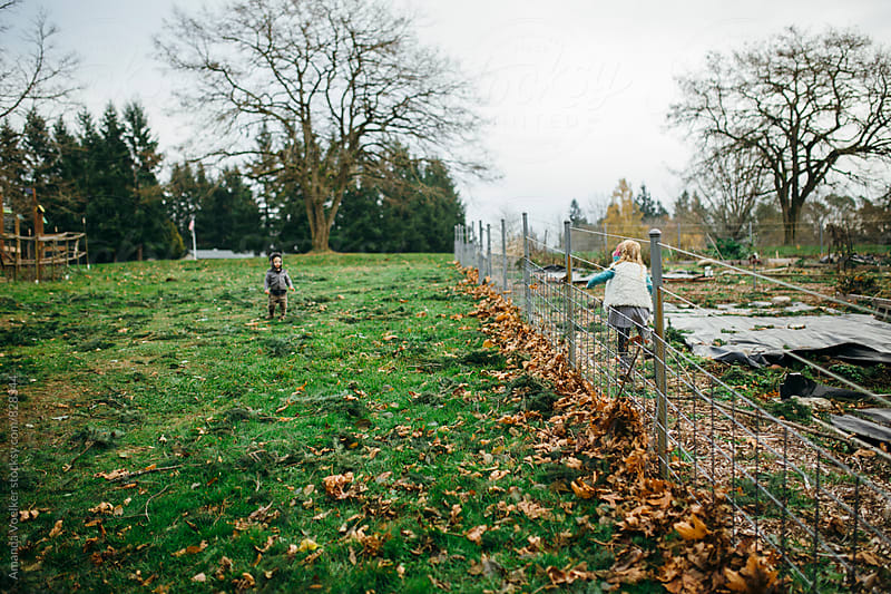 Two Young children play on opposite sides of a fence by Amanda Voelker for Stocksy United