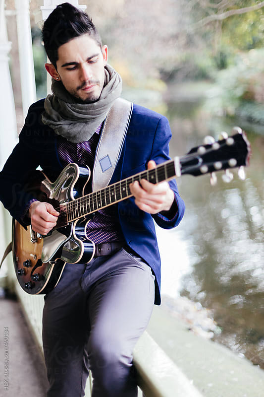 Young Elegant Man Playing Guitar in the Park by HEX. for Stocksy United