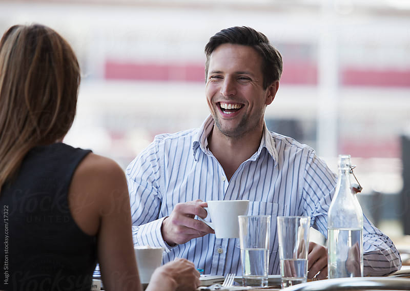 Young professionals meeting in busy cafe or restaurant.  by Hugh Sitton for Stocksy United