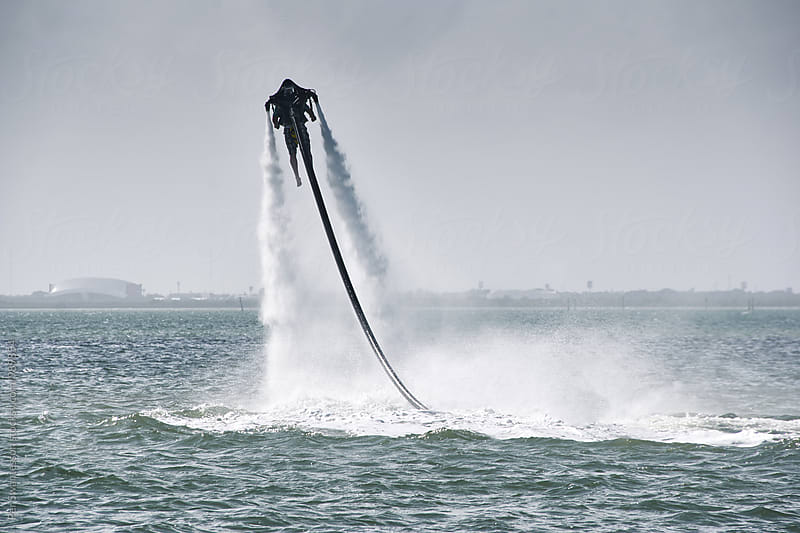 Beach holiday goes high tech - Man having a thrill with a rented water jet pack by Per Swantesson for Stocksy United