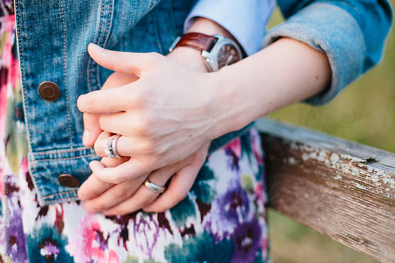 married couple holding hands with rings by Brian Powell for Stocksy United