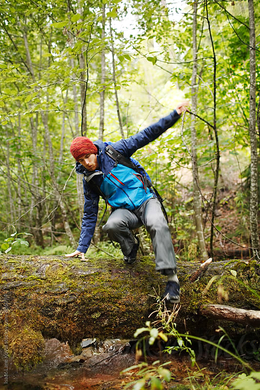 Male hiker jumping over log by Isaac Lane Koval for Stocksy United