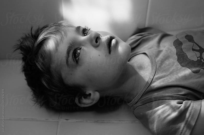 Black and white close up of thoughtful boy laying on bathroom floor. by Julia Forsman for Stocksy United