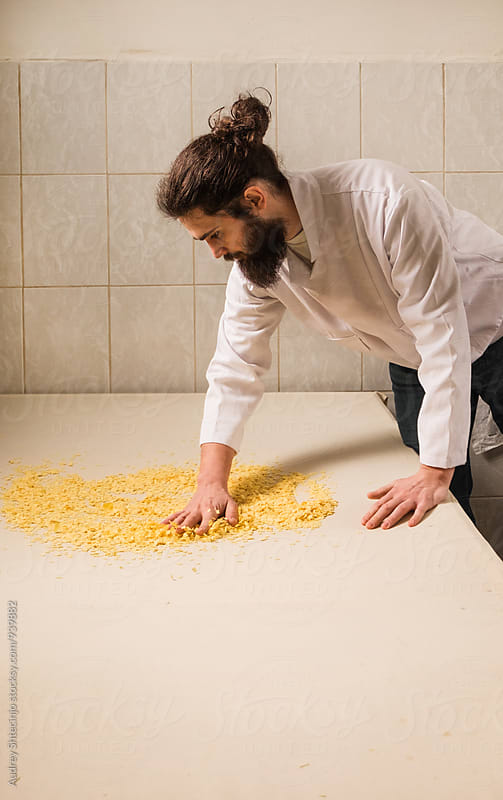 Young man making pasta and noodles in old traditional way. by Marko Milanovic for Stocksy United