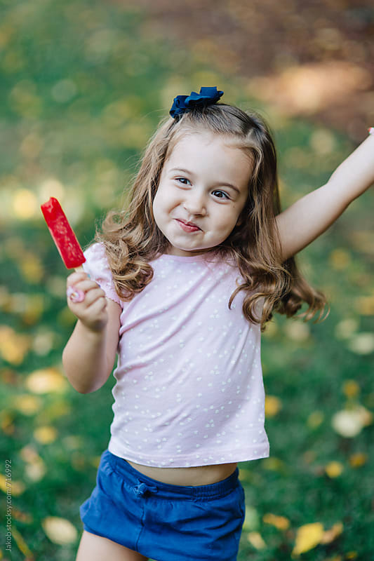 Happy young girl dancing while eating a popsicle by Jakob for Stocksy United