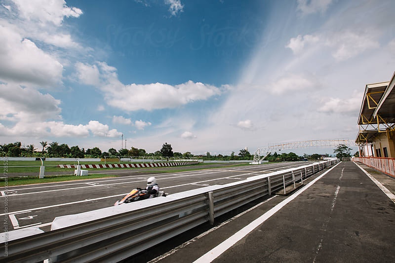 A kart driver zooms past near the start/finish line in racing circuit by Lawrence del Mundo for Stocksy United