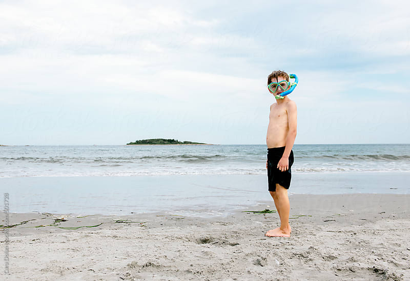 Boy at the beach wears snorkel and mask by Cara Dolan for Stocksy United