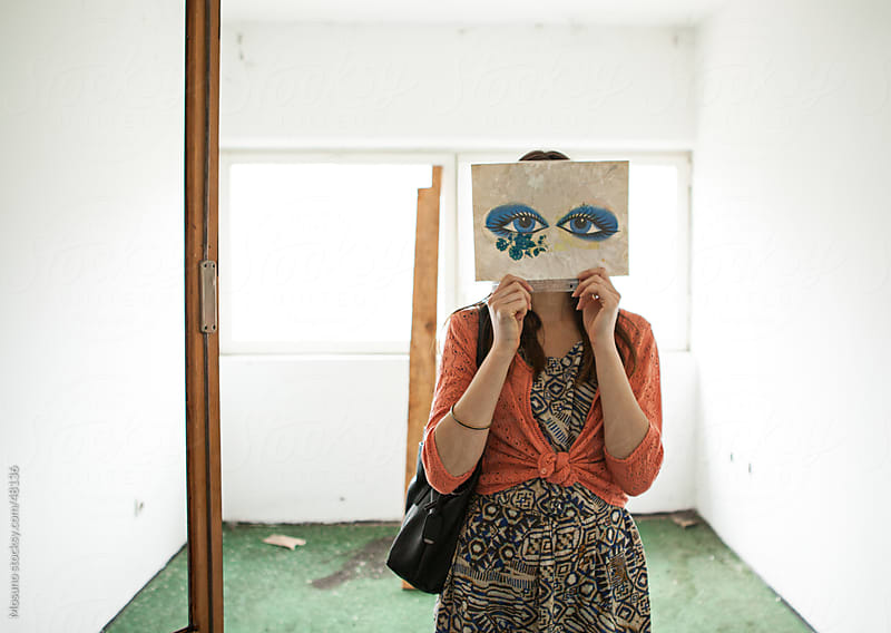 Woman holding paper with drawn eyes in front of her face.  by Mosuno for Stocksy United