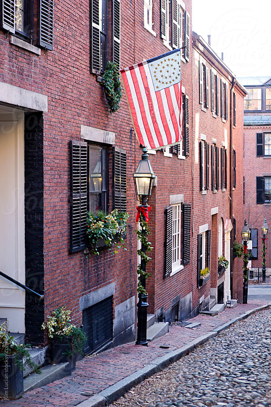 Cobblestone street with flag by Kim Lucian for Stocksy United