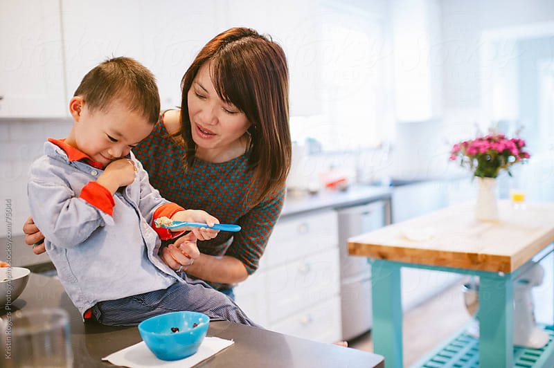 Mother helping son eat breakfast in kitchen by Kristin Rogers Photography for Stocksy United