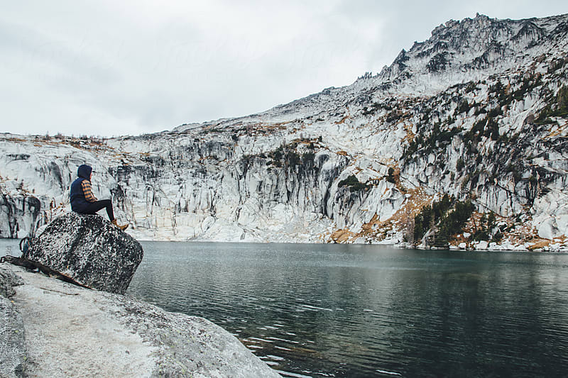 Woman sits on rock above teal-gray lake in rugged landscape by Tari Gunstone for Stocksy United