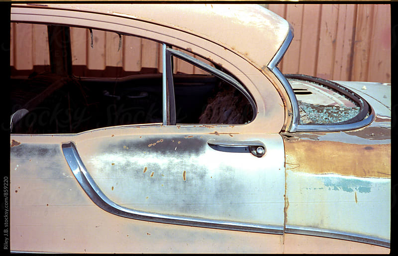 The rear door of an old beat up classic car by Riley J.B. for Stocksy United